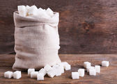 Refined sugar in bag on wooden background — Stock Photo