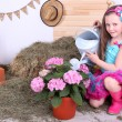 Beautiful small girl in petty skirt holding watering can on country style background — Stock Photo #53086891