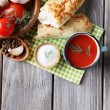 Homemade tomato juice in color mug, bread sticks, spices and fresh tomatoes on wooden background — Stock Photo #53175497