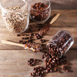 Glass jars and spoon with coffee beans on wooden background — Stock Photo #53178627