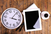 Tablet, cup of coffee, notebook and clock on wooden background — Stock Photo