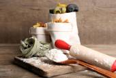Assortment of colorful pasta in bags, rolling-pin on cutting board, on wooden background — Stock Photo