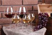 Bottle and glasses of wine and ripe grapes on table on brick wall background — Stock Photo