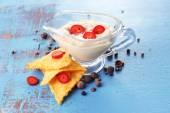 Saborosos nachos e tigela com molho no fundo de madeira de cor — Fotografia Stock