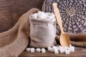 Refined sugar in bag on wooden background — Stockfoto