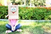 Mujer con caja de cartón en la cabeza con cara feliz, al aire libre — Foto de Stock