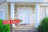 Real estate sign in front of new house for sale — Stock Photo