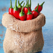 Red hot chili peppers in sack on wooden background — Stock Photo #53235163