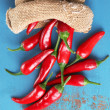 Red hot chili peppers in sack on wooden background — Stock Photo #53235177