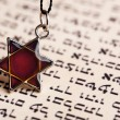 Star David pendant on old paper page background — Stock Photo #53235453