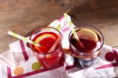 Glasses of cold berry cocktail with lemon on wooden background — Stockfoto
