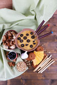 Fondue, olives, slices of cheese, rusks and spices on napkin on wooden background — Stock Photo