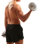Handsome young muscular sportsman execute exercise with dumbbells isolated on white — Stock Photo