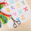 Handmade embroidered letters on white fabric and scissors on wooden background — Stock Photo #53290345