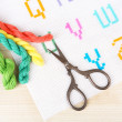 Handmade embroidered letters on white fabric and scissors on wooden background — Stock Photo #53290365