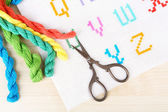Handmade embroidered letters on white fabric and scissors on wooden background — Stock Photo