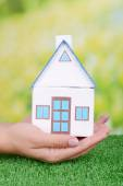 Woman hand holding small house — Stock Photo
