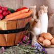 Big round basket with dried grass, vegetables, milk and fresh eggs on sacking background — Stock Photo #53406483
