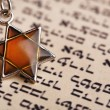 Star David pendant on old paper page background — Stock Photo #53435415