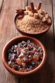 Brown sugar cubes, reed and crystal sugar in bowls on wooden background — Stockfoto