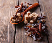 Brown sugar cubes, reed and crystal sugar, spices on wooden background — Stockfoto