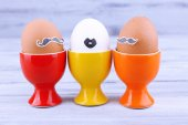 Τα αυγά στο αυγό κύπελλα σε γκρι φόντο ξύλινη — 图库照片