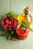 Sun dried tomatoes in glass jar, olive oil in glass bottle, basil leaves on color wooden background — Stock Photo