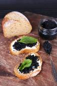 Slices of bread with butter and black caviar on wooden background — Stock Photo
