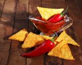 Tasty nachos and bowl with sauce on wooden background — Stock Photo