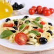 Spaghetti with tomatoes, olives, olive oil and basil leaves on plate on fabric background — Stock Photo #53696331