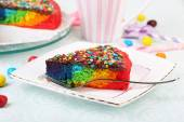Delicious rainbow cake on plate and cup with coffee, on table, on light background — Stock Photo