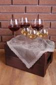 Glasses of wine on box on brick wall background — Stock Photo