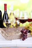 Bottles and glasses of wine and ripe grapes on table on natural background — Foto de Stock