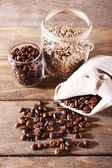 Coffee beans in fabric bag and glass jars on wooden background — Stock Photo