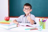 Schoolboy sitting in classroom — Stock Photo
