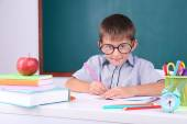 Schoolboy sitting in classroom — Stock Photo