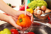 Woman's hands washing vegetables — Stock Photo