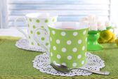 Two cups with sugar and wildflowers on napkin on table on light background — Stock Photo