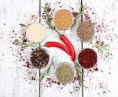 Spices in glass round bowls with herbs and chilly pepper on wooden background — Stock Photo