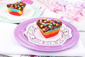 Läckra regnbåge kakor på tallrikar, på färg trä bakgrund — Stockfoto