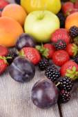 Ripe fruits and berries on wooden background — Stock Photo