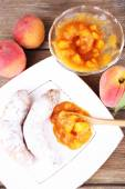 Tasty peach jam with fresh peaches and croissants on wooden table — Stock Photo