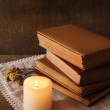Books, flowers and candle on napkin on wooden table on wooden wall background — Stock Photo #53861773