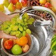 Woman's hands washing grapes and other fruits in colander in sink — Stock Photo #53864121