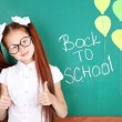 Cute girl standing near blackboard in classroom — Stock Photo #53864631