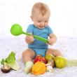Cute baby boy with fruit and vegetables on carpet in room — Stock Photo #53865033
