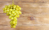 Bunch of grape on wooden background — Stock Photo