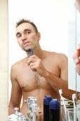 Young man shaving his beard in bathroom — Stock Photo