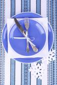Blue plates, knife, fork, napkin and Christmas decoration on tablecloth — Foto de Stock