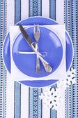 Blue plates, knife, fork, napkin and Christmas decoration on tablecloth — Zdjęcie stockowe